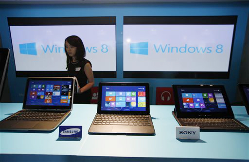 A woman walks past laptop computers running Microsoft Windows 8 operating system during the software's launching ceremony in Hong Kong in October 2012.