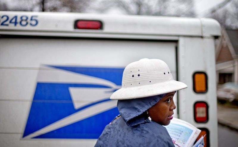 In this Feb. 7, 2014 file photo, U.S. Postal Service letter carrier Jamesa Euler, delivers mail in the rain in the Cabbagetown neighborhood, in Atlanta. The U.S. Postal Service says it will delay plans to cut Saturday mail delivery because Congress isn't allowing the change. The Postal Service said in February that it planned to cut back in August to five-day-a-week deliveries for everything except packages, as a way to hold down losses. (AP Photo/David Goldman)