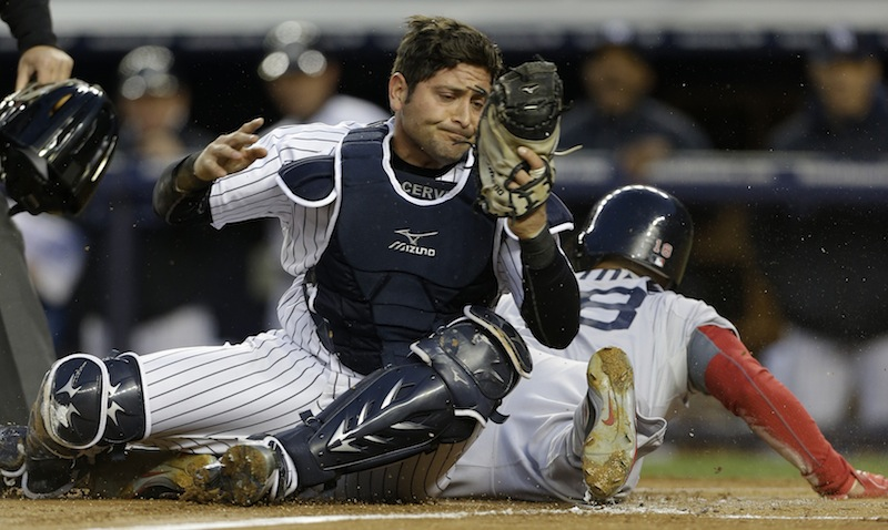 New York Yankees catcher Francisco Cervelli, left, reacts after tagging out Boston Red Sox Shane Victorino, right, who was trying to score on a wild pitch in the first inning of a baseball game at Yankee Stadium in New York on Thursday.