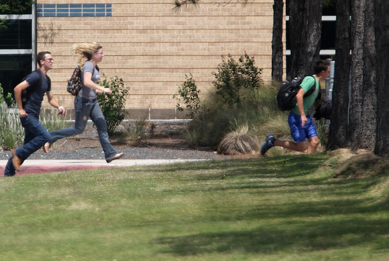Students run from the Lone Star College's Cy-Fair campus in Cypress, Texas, where a student went on a building-to-building stabbing attack Tuesday, April 9, 2013. The attacker wounded at least 14 people before being subdued and arrested, authorities said. (AP Photo/Houston Chronicle, James Nielsen)