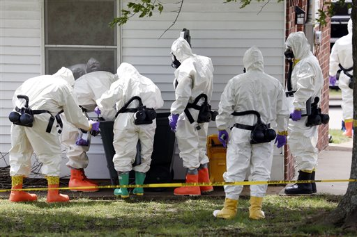 Federal agents wearing hazardous material suits inspect a trash can on Friday outside the house of Paul Kevin Curtis in Corinth, Miss. Curtis is in custody under the suspicion of sending letters covered in ricin to President Barack Obama and U.S. Sen. Roger Wicker, R-Miss.