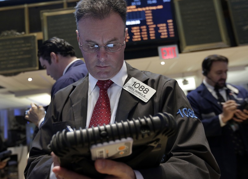 The handheld device of trader Joseph Tarangelo, center, is reflected in his glasses as he works on the floor of the New York Stock Exchange Monday, April 29, 2013. A pair of encouraging economic reports helped propel the stock market up in early trading on Monday. (AP Photo/Richard Drew)