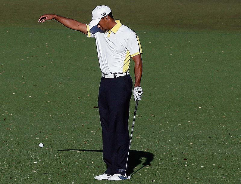 Tiger Woods takes a drop on the 15th hole after his ball went into the water during the second round of the Masters golf tournament Friday. On Saturday, Woods was slapped with a two-stroke penalty.