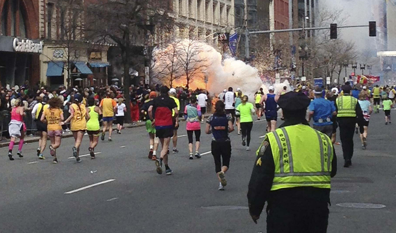 In this Reuters photo from Monday, runners continue to run towards the finish line of the Boston Marathon as an explosion erupts near the finish line. A congressman says investigators still don't know whether the Boston Marathon bombs were the work of domestic or foreign attackers. (REUTERS/Dan Lampariello)