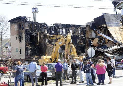 Spectators watch demolition efforts Tuesday at the scene of the fire that heavily damaged three apartment buildings Monday in Lewiston.