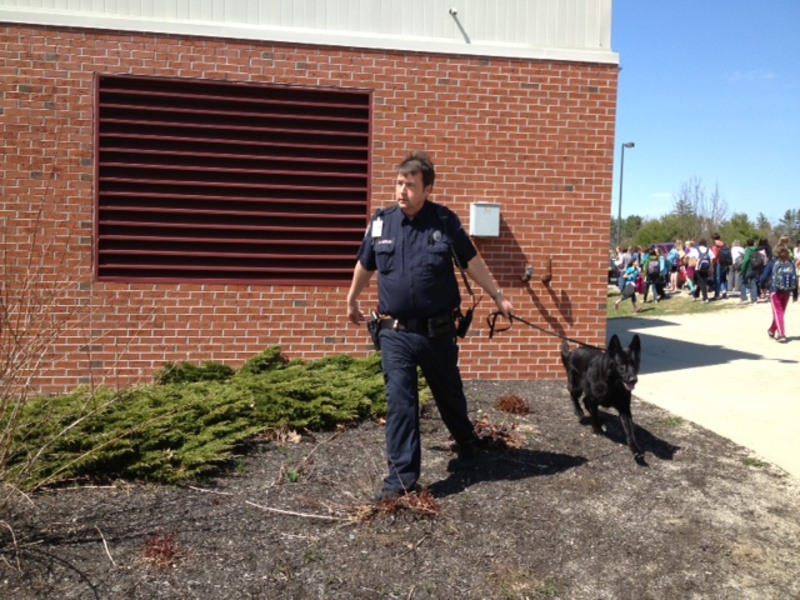 A Portland police officer and his bomb-sniffing dog assist the Gorham Police Department in investigating a bomb threat at Gorham Middle School on Friday.