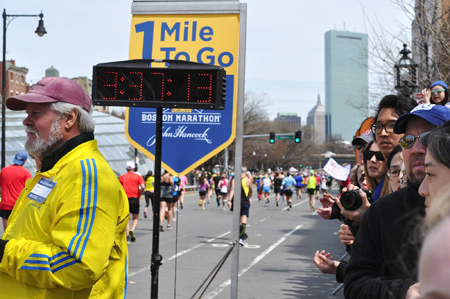"""Onlookers watch as runners cross the """"1 Mile To Go"""" marker shortly after 12 p.m. Monday at the Boston Marathon. Just before 3 p.m., two bombs exploded 12 seconds apart at the marathon finish line, killing three and injuring 176 others."""