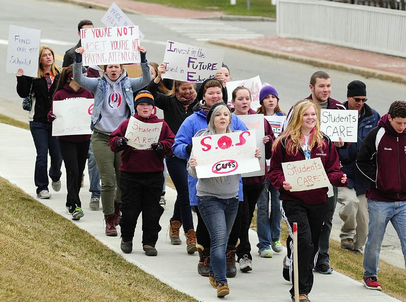 Students march along Capital Street between State House and Blaine House during a protest on Friday at the State House in Augusta.