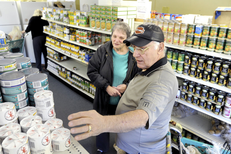 Volunteer George Coburn assists Eleanor Locey of Saco select groceries at the Saco Food Pantry last week.