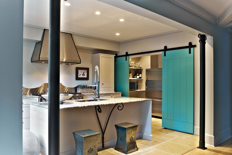 Sliding doors bring a unique look to a room and can be larger and heavier than swinging doors. Blue planks hanging from exposed hardware bring a burst of color and functionality to a kitchen space in this version from Eddie DeRhodes Builder.