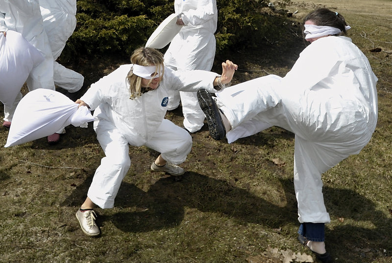 Employees of Cuddledown in Yarmouth, nicknamed the 'Cuddledown Ninjas, ' practice their pillow-fighting tactics outside their facility in preparation for the Portland Pillow Fight Day that will happen at Monument Square on Saturday, April 6. Some took the Ninja title to heart and started using their feet to fend off an attacker.