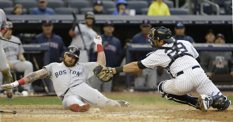 Boston's Jonny Gomes beats the tag of Yankees catcher Francisco Cervelli as he scores on a single by Jacoby Ellsbury in the ninth inning at New York.