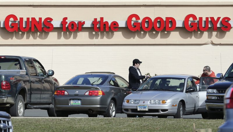 Shoppers leave Hoffman's Gun Center on Tuesday in Newington, Conn. Customers are packing gun stores in the state after the unveiling of new gun-control legislation.