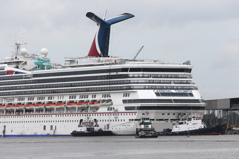 Tug boats maneuver around the Carnival Triumph as it rests against a dock on the Mobile River after becoming dislodged from its mooring during high winds Wednesday.