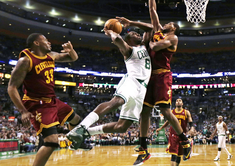Boston Celtics forward Jeff Green (8) tries to get his shot off as he is pressured by Cleveland Cavaliers forward Tristan Thompson, right, in Boston Friday. At left is Cavaliers forward Alonzo Gee (33).