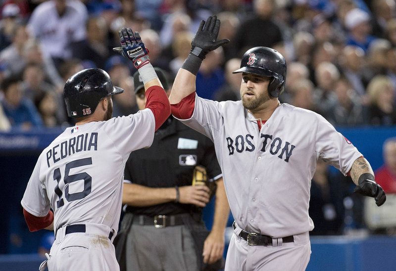 Boston's Mike Napoli gets a welcome at home plate from Dustin Pedroia after his two-run homer in the fifth inning of a 6-4 Red Sox win at Toronto on Friday. Napoli later drove in the go-ahead run.