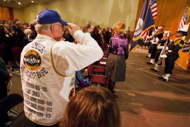 Hundreds gathering at Portsmouth High School, including former USS Thresher crew member Robert J. Miller, left, salute the flag to begin Saturday's memorial ceremony.