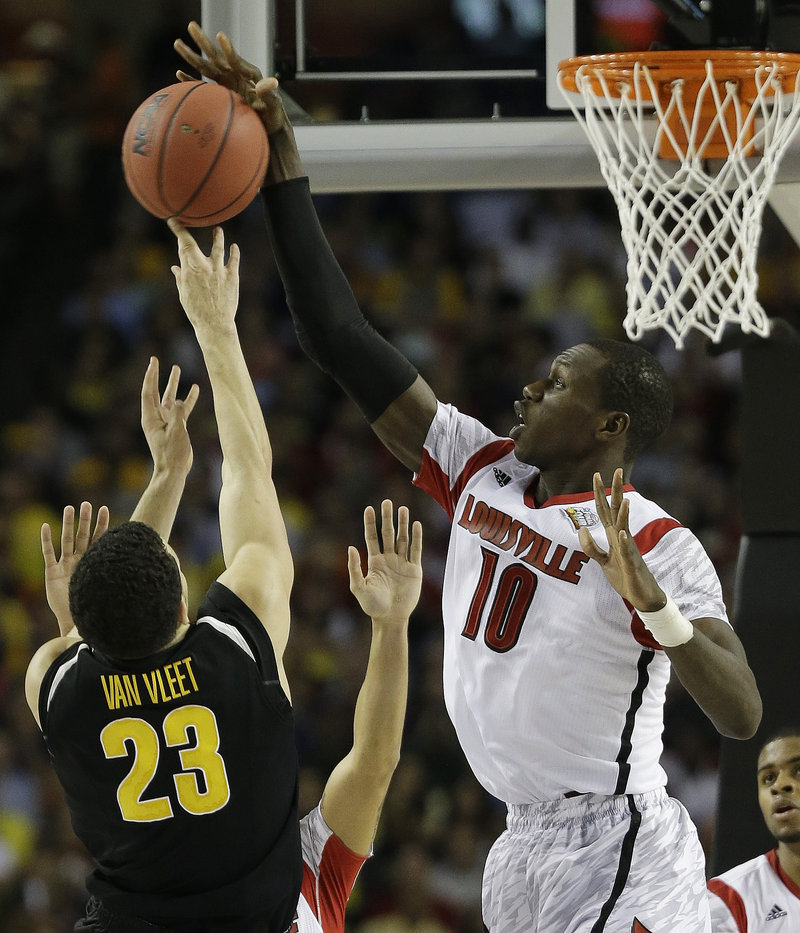 Gorgui Dieng of Louisville knocks away a shot by Fred Van Vleet of Wichita State during Louisville's come-from-behind 72-68 victory Saturday night in the national semifinals.