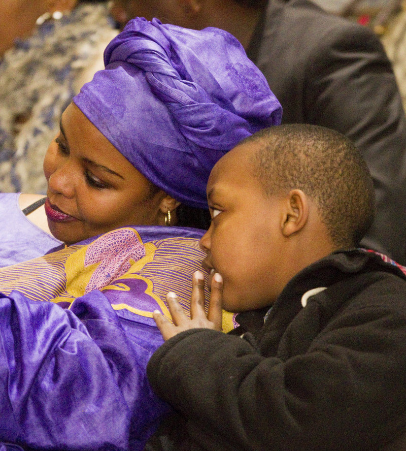 Daniel Bizimana whispers to his mother, Francoise Nsengiyumva, during a ceremony in Portland Sunday.