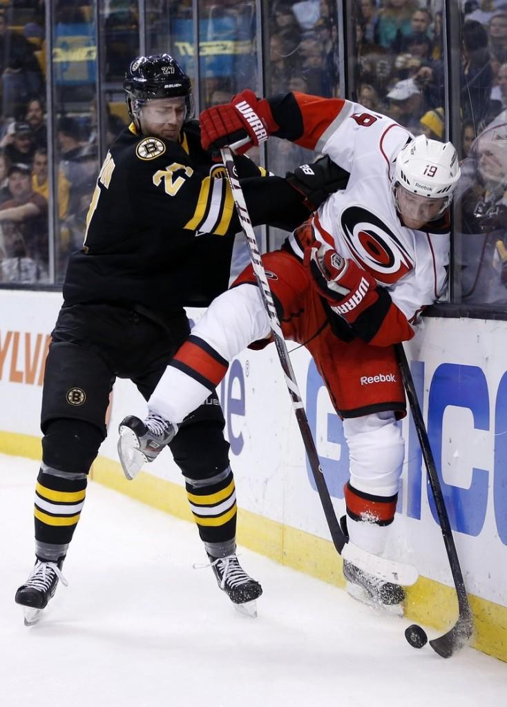 Dougie Hamilton of the Bruins slams Carolina's Jiri Tlusty into the boards Monday night in Boston. The Bruins scored a season-high six goals in beating the Hurricanes.
