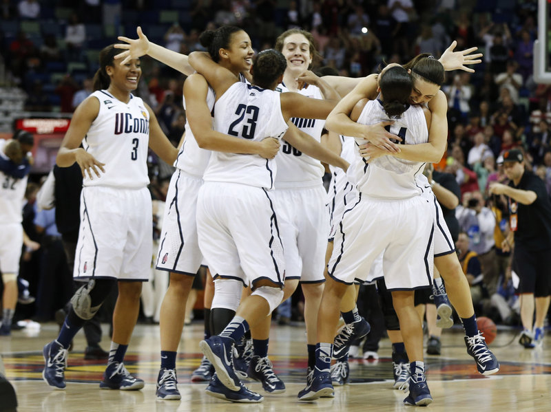 Connecticut players celebrate after defeating Louisville 93-60 for the national women's basketball championship Tuesday in New Orleans. UConn is now tied with Tennessee for the most titles, eight.