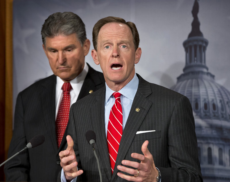 In Washington, Sen. Joe Manchin, D-W.Va., listens as Sen. Patrick Toomey, R-Pa., discusses the deal they reached on expanding background checks to more gun buyers.