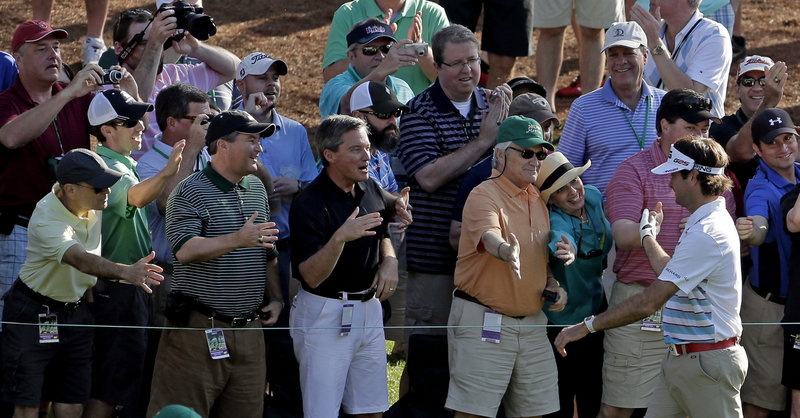 Bubba Watson is congratulated by spectators after a hole-in-one on the 16th hole during a practice round for the Masters golf tournament Wednesday in Augusta, Ga.