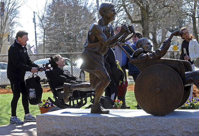 In this April 8, 2013, file photo, Dick Hoyt, left, talks with his son Rick as he wheels him next to a statue dedicated in their honor in front of the Center School in Hopkinton, Mass.