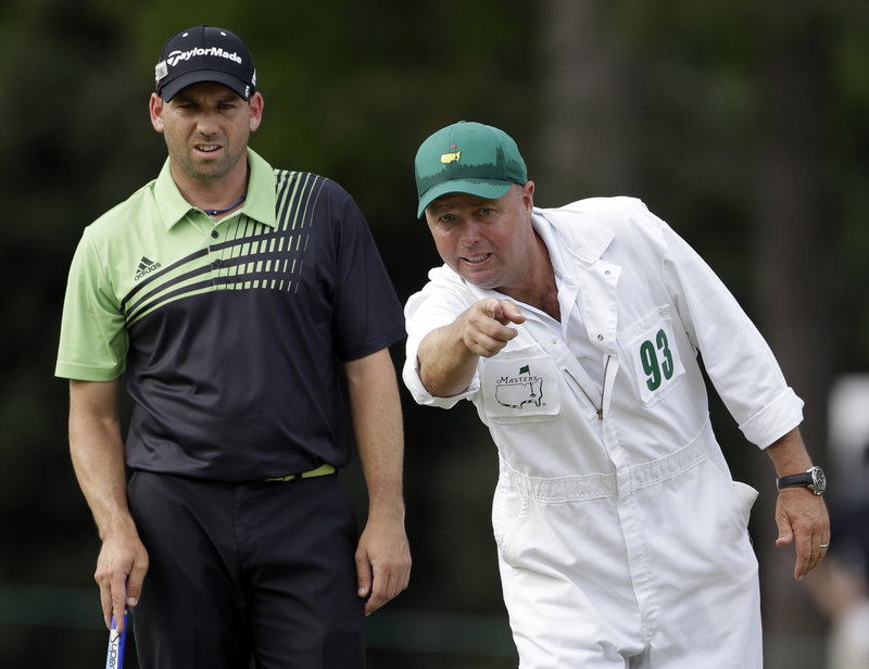 Sergio Garcia, who doubted last year he ever could win a Masters, listens to his caddie, Greg Hearmon, during his first-round 66 on Thursday. Garcia is tied for the lead.