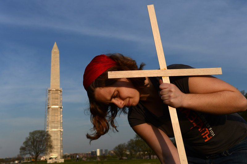 Janelle Tupper places a cross, one of about 3,300 symbolic markers assembled Thursday on the National Mall in Washington to represent victims of gun violence that occurred after the December 2012 shootings in Newtown, Conn.