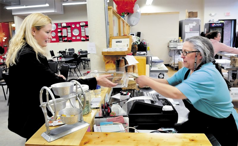 The Button-Down Cafe owner Maureen Kibler, right, gives change to customer Sarah Brown at the new restaurant in the Hathaway Creative Center in Waterville. The Button-Down Cafe is one of three new downtown eateries livening up the scene in Waterville.