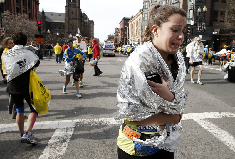 A Boston Marathon runner cries as she leaves the course near Copley Square on Monday.