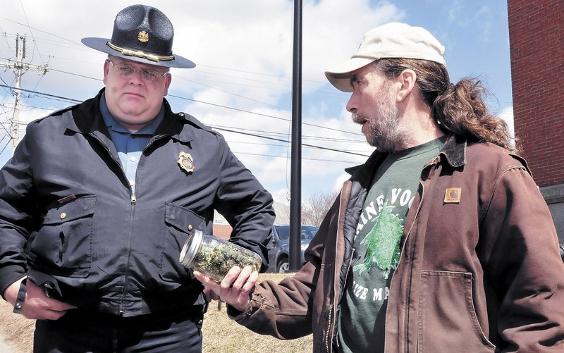 """Marijuana advocate Donald Christen shows a jar of the weed to Skowhegan Deputy Police Chief Dan Summers during the Patriots Day """"smoke-in"""" on the steps of the Somerset County Courthouse. The event is staged annually to support full legalization of the drug."""
