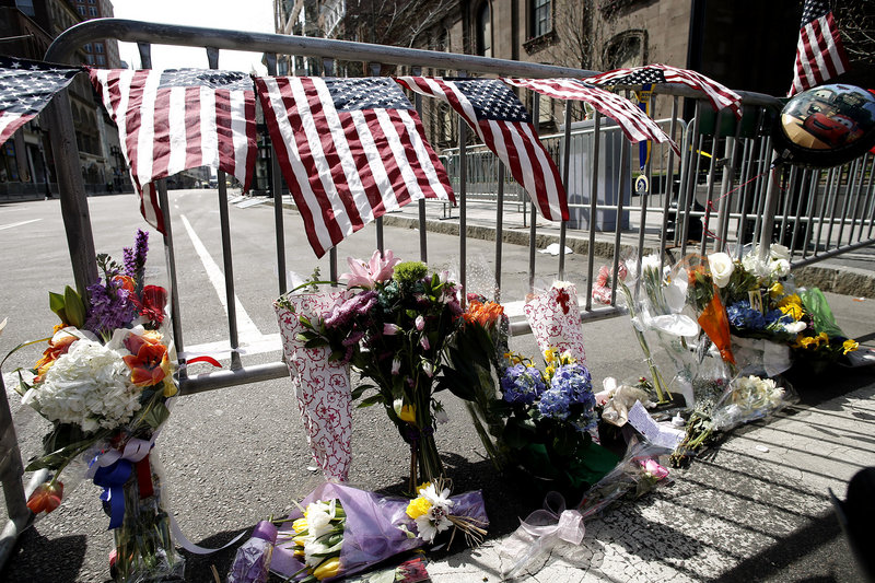 Flowers are placed by a Boston police barricade near the finish line of the Boston Marathon in Boston, Tuesday, April 16, 2013.