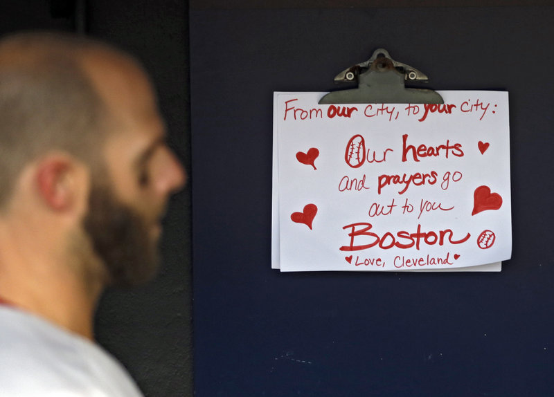 Dustin Pedroia of the Red Sox walks past a condolence sign in the dugout. The sign was written by a young Cleveland fan.