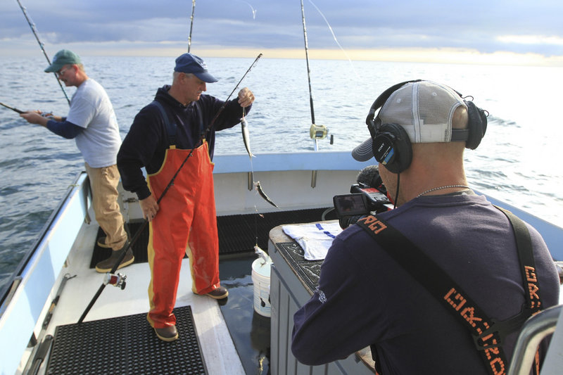 """Cameraman River Hagg films first mate Bruce Hebert of North Waterboro, second from left, as he rigs bait fish with deckhand Kevin Twombly, left, aboard the fishing boat Lisa & Jake in Gloucester, Mass., on the current season of """"Wicked Tuna,"""" airing on the National Geographic Channel."""