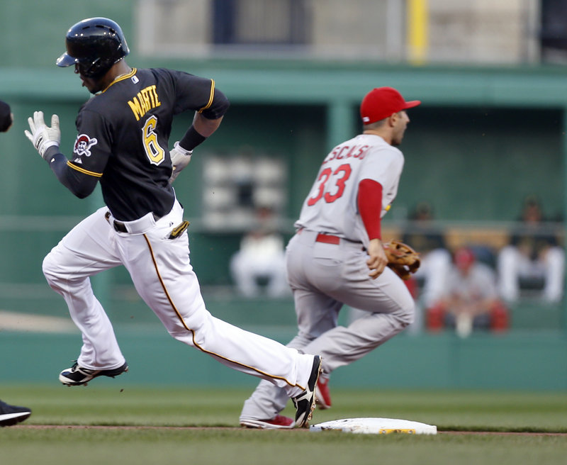 Starling Marte of the Pittsburgh Pirates rounds second behind Daniel Descalso of the St. Louis Cardinals on his way to a triple.