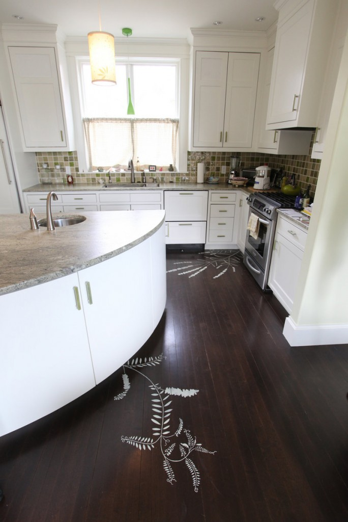 Stenciled images of plants in the floor and a wedge-shaped island are among the creative touches in the kitchen of an Eastern Prom home that is on the tour.