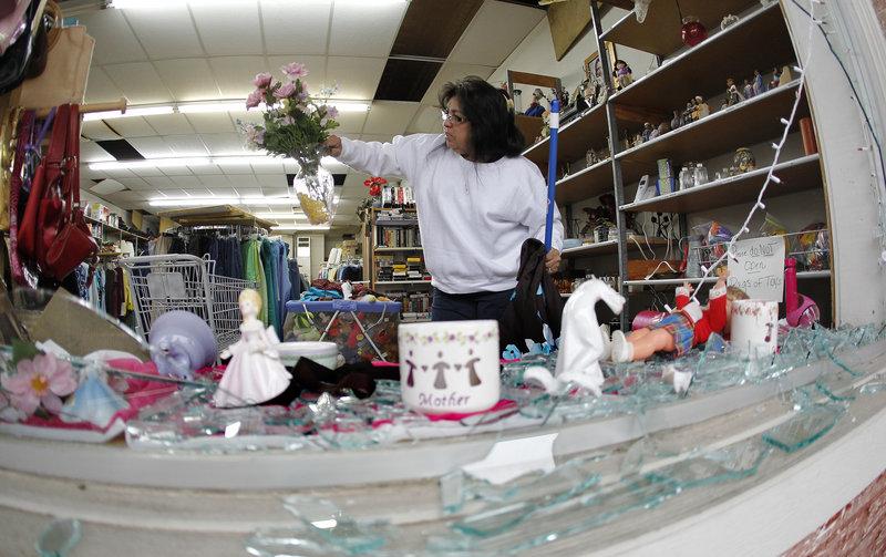 Maria Galvan sorts through damaged merchandise inside the West Thrift Shop on Thursday.