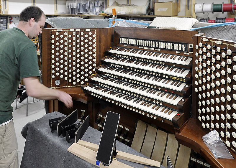 """Adam Loagocki works on the console of Portland's Kotzschmar Organ. He is part of a team of experts who will make the organ """"sing"""" again."""