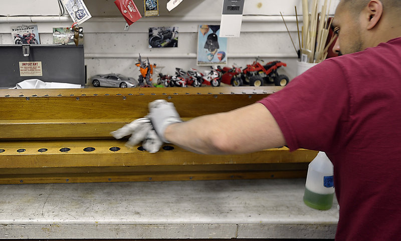 Mee Racz works to prepare the organ's offset chest for refinishing, as part of the organ restoration project.