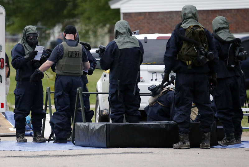 Federal agents wearing hazardous material suits and breathing apparatus begin cleaning up after searching the home of Paul Kevin Curtis in Corinth, Miss., Thursday evening.