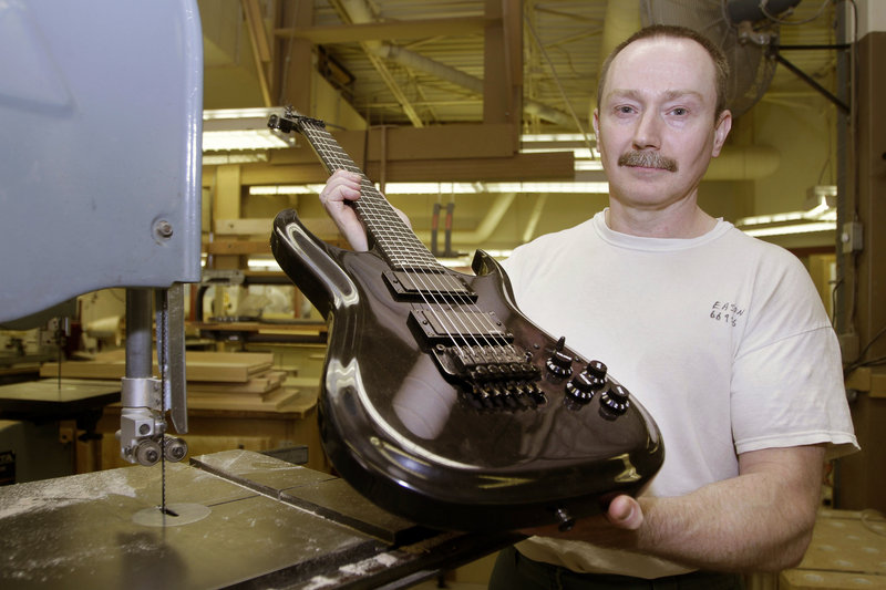 """Allen Eason poses with a guitar he made. Eason is a master furniture maker and a convicted murderer without the possibility of parole. """"This is my life,"""" Eason said."""