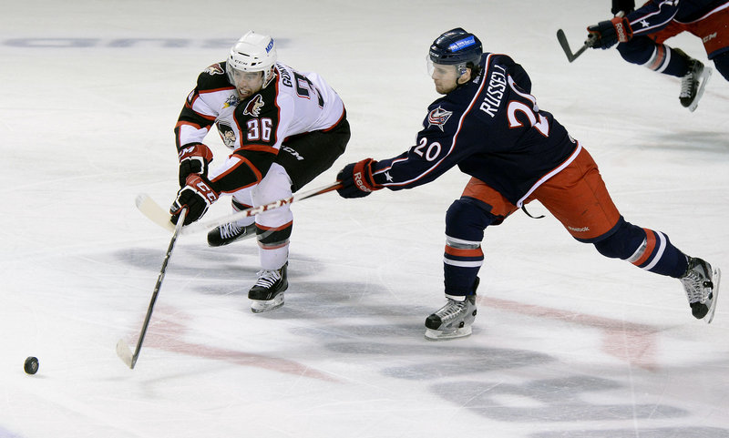 Brandon Gormley of the Portland Pirates battles for the puck against Ryan Russell of the Springfield Falcons on April 7.