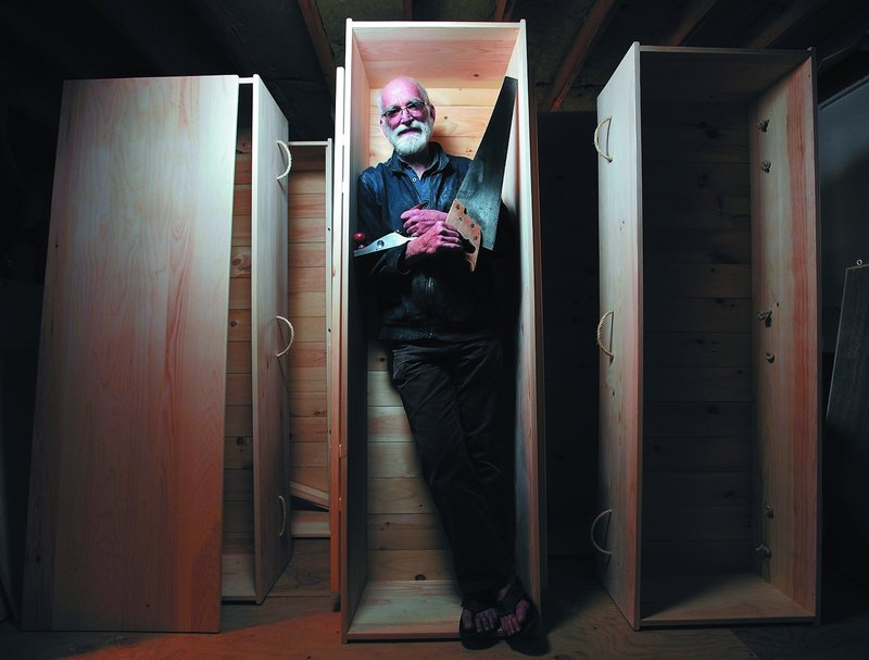 """Chuck Lakin stands inside a coffin in the basement workshop of his Waterville home Saturday. """"Americans are really good at ignoring the fact that they're going to die,"""" he said."""