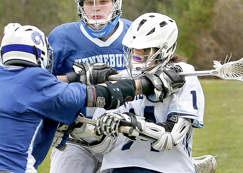 Jesse Shields, left, of Kennebunk uses his stick to harass Tyler Jack of Westbrook during Saturday's lacrosse game in Westbrook. Kennebunk cruised to a 12-1 victory.