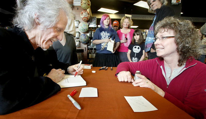 """John Densmore signs a copy of his book, """"The Doors Unhinged,"""" for Leslie Bruenn of Cobalt, Conn., at Bull Moose. She and her husband, Carl Bruenn, were the first ones in line, at 9 a.m. for the 2 p.m. event."""