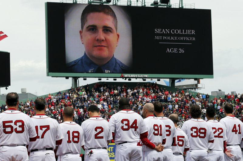 The Boston Red Sox line up during an emotional tribute to victims and survivors of the Boston Marathon bombings, as an image of slain Massachusetts Institute of Technology Police Officer Sean Collier is displayed on the scoreboard. Collier was killed in a confrontation with the bombing suspects Thursday night.
