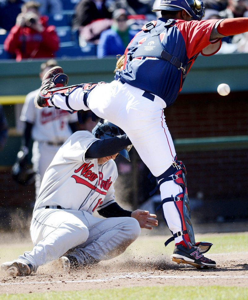 New Britain's Nate Hanson slides safely into home as Sea Dogs catcher Alberto Rosario tries to field the throw during Sunday's game at Hadlock Field. The Sea Dogs won, 8-7.