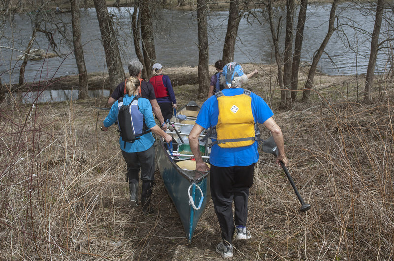 A voyageur canoe needs all of its crew to help with a portage – a group effort seen here at 6 Mile Falls on the Kenduskeag.